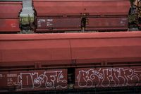 many red train containers on railroad