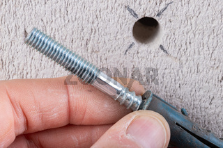 Hole in the wall, screw and dowel for fixing in concrete. Wall mounting methods.