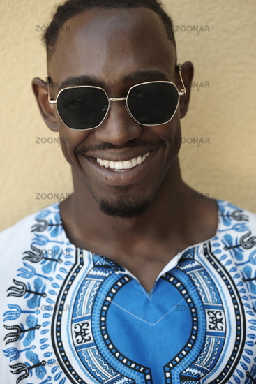 portrait of a smiling young african man wearing traditioinal clothes