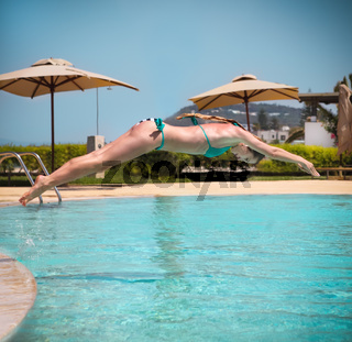 Girl jumping to a swimming pool