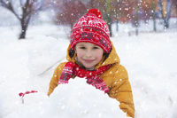 Child in winter. A happy boy in bright clothes plays in the snow.