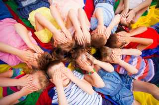 Children laying very closely, covering face by hands