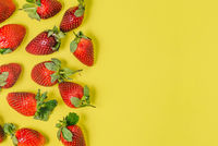 Strawberries on a yellow background. Ripe and fresh red berries with a high content of vitamins. The concept of Valentine's Day, love and relationships. Top view, copy space.