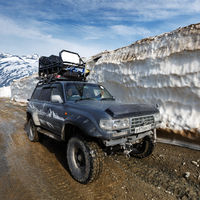 Japanese sport utility vehicle Toyota Land Cruiser driving on mountain road in snow tunnel