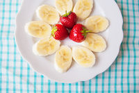 banana and strawberries on a white plate and a colorful napkin.