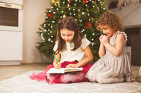 Two cute little sisters writing a letter to Santa