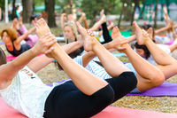legs and feets of people in dhanurasana yoga pose in park outdoor
