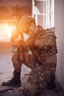 soldier in action near window changing magazine and take cover