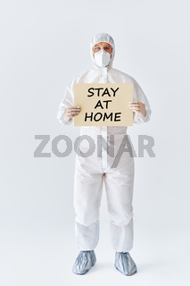 Doctor in protective medical suit showing blank placard stay at home