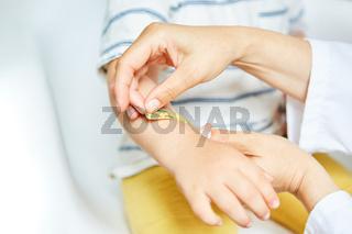 Kinderarzt klebt ein Pflaster auf Hand mit Prellung