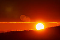 Beautiful sunrise in mountains, red sun disk rises from tops of mountain range. Natural lens flare