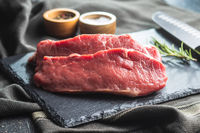 Slices raw striploin steak on black stone cutting board.