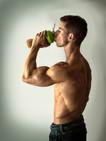 Young muscular man drinking protein shake in studio