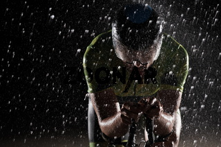 triathlon athlete riding bike  fast on rainy night