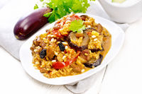 Rice with vegetables and chicken in plate on light wooden board