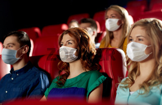 people in masks watching movie in theater