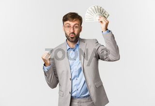 Successful bearded businessman in grey suit and glasses, winning cash, holding money and triumphing, standing happy over white background