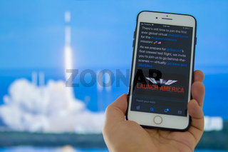 Kennedy Space Center, Florida, United States. May 27, 2020. A person holding a iPhone with the Launch America logo with an out of focus rocket launch background