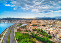 Aerial drone view Majorca cityscape, road along the coast of Mediterranean sea and famous Cathedral of Palma de Mallorca or Le Seu. Cloudy moody sky, mountain valley. Balearic Islands. Spain