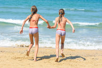 Two little sisters running to swim in the sea, back visas