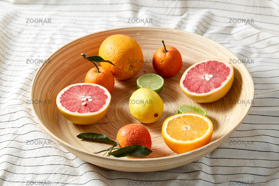 close up of citrus fruits on wooden plate