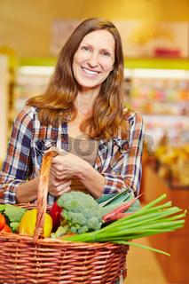 Frau trägt Einkaufskorb voll Gemüse