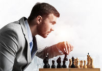 Businessman moving chess figure in chessboard