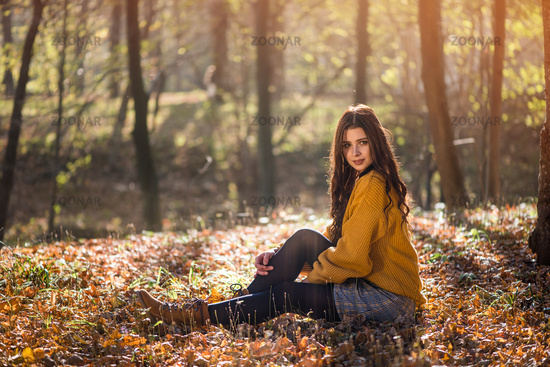 Young beautiful caucasian woman sits on the ground in a autumn park among high trees