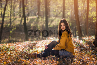 Young beautiful caucasian woman sits on the ground in a autumn park among high trees. Mysterious and seductive look of a beautiful woman