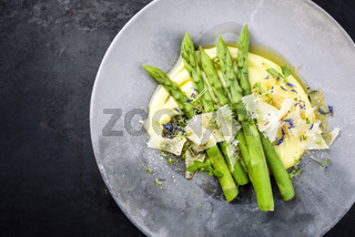 Traditional steamed green asparagus with mashed potato creme and parmesan as top view on a modern design plate with copy space left