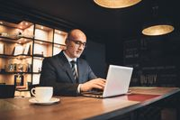 Middle aged businessman in business suite and eye glasses working using laptop in modern office at late. Tired businessman working late night. Handsome bold man working on laptop in office