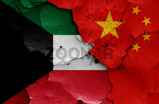 flags of Kuwait and China painted on cracked wall