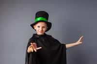 Little magician does tricks. Little boy wears costume magician and magic hat.
