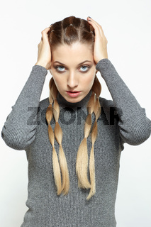 Portrait of blonde female with creative braid hairdo with hands on head.