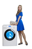 woman in a dress with a stack of towels next to a new washing machine, isolated on white background