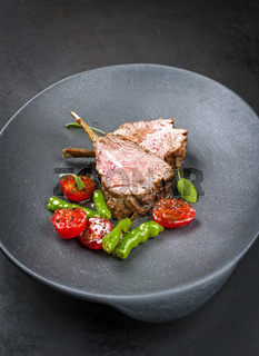 Barbecue rack of lamb neck with paprika and tomato offered as closeup on a modern design plate