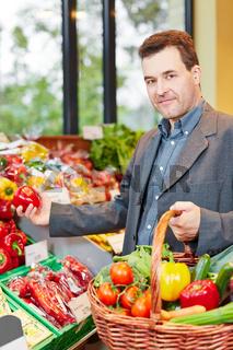 Mann kauft Gemüse im Biomarkt