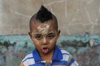 Yangon, Myanmar, Portrait eines kleinen Jungen mit Thanakapaste Make-up im Gesicht