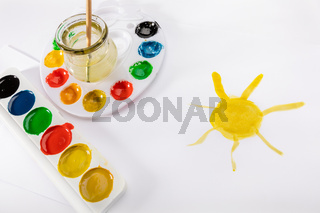 Kids painting concept - a drawing, watercolor palletes and a paint brush, isolated on a white background