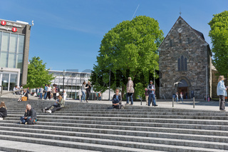 People relaxing and sitting on stairs in front of Stavanger Cathedral in Stavanger Norway