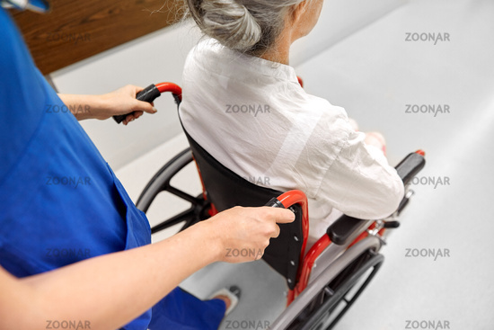 nurse with senior patient in wheelchair at clinic