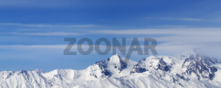 Panoramic view on high snowy mountains and blue sky with clouds