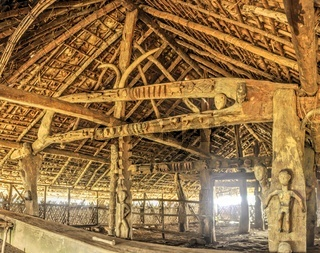 Interior of a traditional wooden dwelling with carved symbols in India