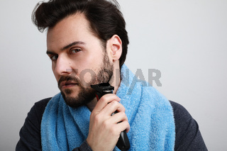 Bearded man shaving in the morning. Isolated over white background.