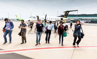 Passengers disembarking a small charter propeller engine airplane at local airport