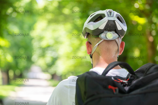 Rear view of unrecognizable man wearing protective helmet on bicycle cycling in city park