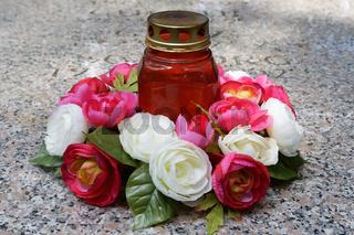 Grabkerze und Rosengesteck