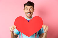 Valentines day concept. Romantic man falling in love, showing big red heart cutout and smiling, standing on pink background
