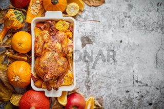 Thanksgiving dinner table with roasted whole chicken or turkey, pumpkin, baked potatoes, chestnuts