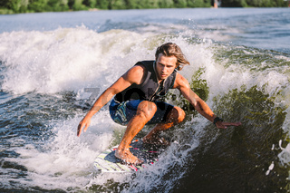 Beautiful long haired blond wakesurf in vest on board along waves of lake. Athletic male athlete wakes surfing in summer on river. Wakesurf water sport. Surfer on wave. Man surfing on the Surfboard